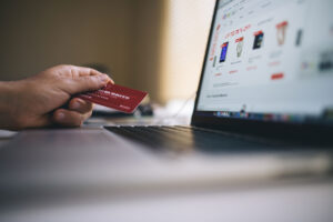 person holding credit card by laptop